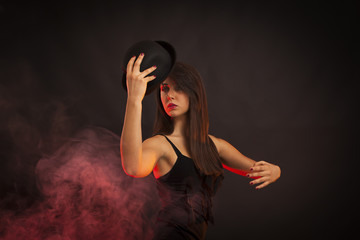 Beauty woman dancing with hat in his hand. Red smoke, black background