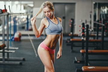 Sexy fitness happy blonde girl in sport wear with perfect body in the gym posing and smiling