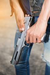 Man in jeans holding a gun