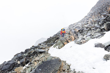 Mountaineer tourist walking mountain trail storm snowing weather