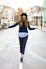 Fashionable young woman balancing on median strip of a road