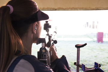 Woman with a sporting rifle in a shooting range