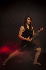 Beauty girl dancing with red rose in his hand. Red smoke, black background