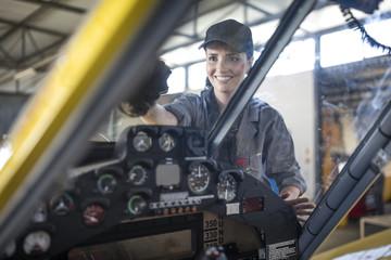 Mechanic in hangar cleaning windscreen of light aircraft