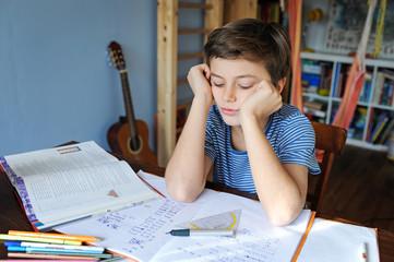 Kind macht Mathematikhausaufgaben und ist beim Rechnen überfordert
