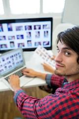 Graphic designer using laptop at his desk