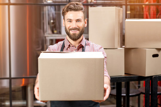 Portrait of professional courier with boxes delivering packages at the manufacturing.