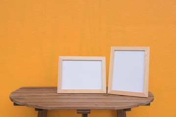 Two photo Frame on a wooden on Yellow background .