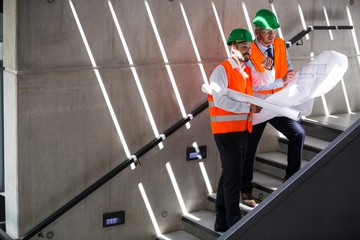 Architects standing on a staircase discussing with blueprint