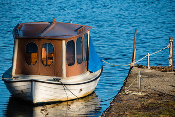Houseboat or up cycled fishing boat as seen from the aft. Boat is tied to a pier in calm water.