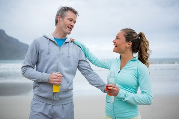 Couple drinking water after exercise on beach