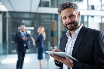 Businessman using digital tablet in office corridor