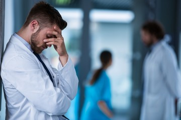 Stressed doctor standing against wall in hospital