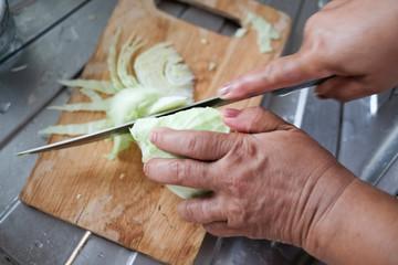 Senior women hands cutting cabbage for salad
