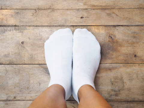 feet wearing white socks on wood