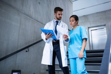 Doctor and nurse discussing over a report