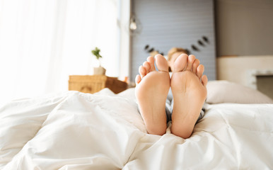Close up of pregnant womans feet lying in bed