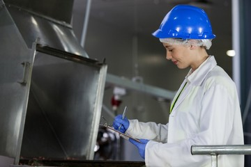 Technician examining meat processing machine
