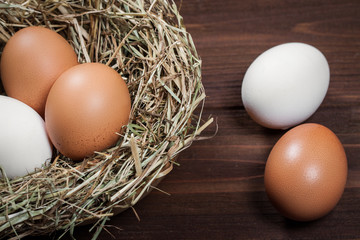 Fresh chicken eggs on a wooden table.
