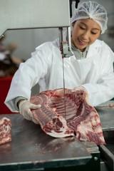Female butcher cutting raw meat on a band saw machine