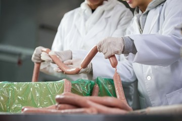 Butchers processing sausages