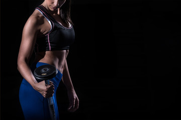 Woman bodybuilder  lifting barbell isolated over black background