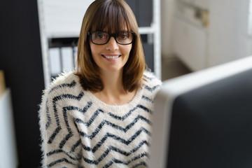 lächelnde frau mit brille arbeitet am computer im büro
