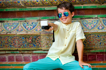Cute little boy in Grand Palace making a self portrait with action camera