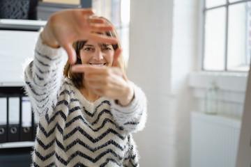 lachende frau im büro bildet einen rahmen mit ihren händen