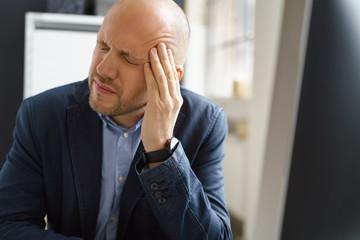 mann sitzt am computer und hat kopfschmerzen