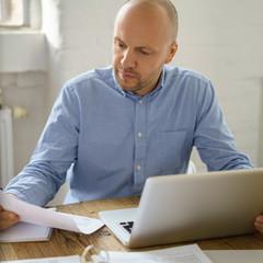 mann sitzt mit laptop und unterlagen zu hause am tisch