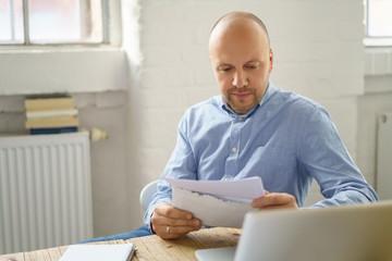 mann sitzt zuhause am tisch und liest einen brief
