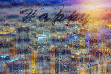 Rainy season with cityscape background, the inscription on the glass.Word happy on window glass.
