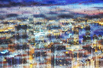 Water drop on glass of window with nightlife cityscape background.