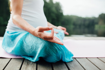 Woman meditating in the lotus position closeup. Hands close-up mudra. Sitting on wooden floor by the river