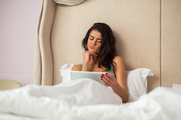 Girl with tablet in bed. Thoughtful woman indoor. List of internet stores.