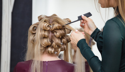 Hairdresser working with hair curlers woman in a beauty salon or barber shop