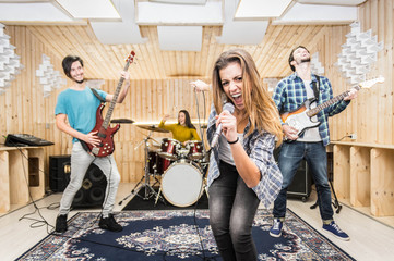 Caucasian music band performing in a recording studio