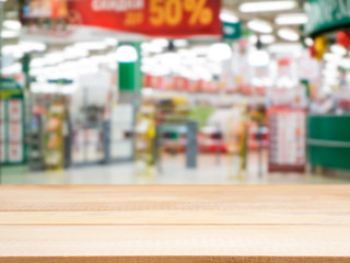 Wooden empty table in front of blurred supermarket entrance area