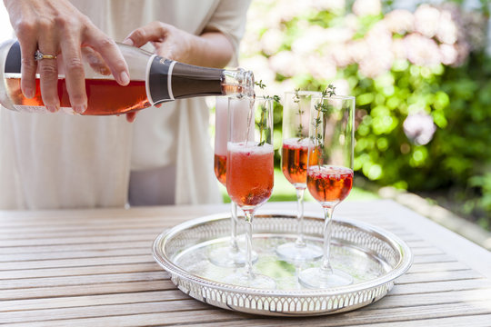 Woman pouring sparkling wine into four glasses