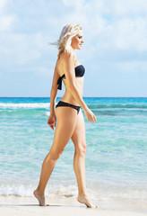 Young woman in a sexy bikini posing on the beach