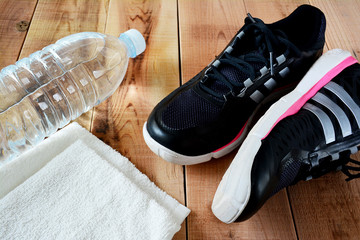 Sport shoes and towel, bottle of water on wooden.