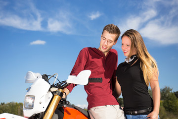 young couple looking sideways standing beside a motorcycle