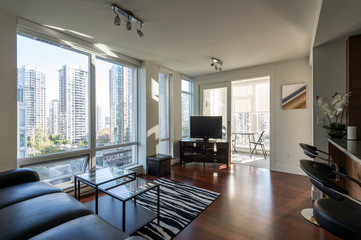Modern apartment living room and kitchen with a view of downtown. Interior design.