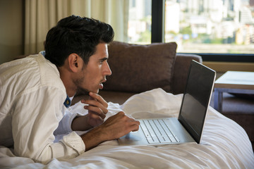 Attractive Young Man with Serious Expression, with Laptop on Bed Working on his Start-up Business - Young Male College or University Student Doing Homework, in Bedroom