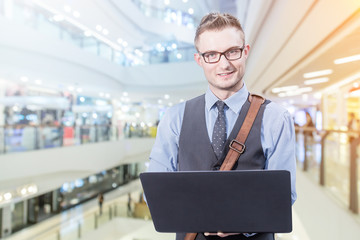 Young handsome businessman standing with laptop in the big city