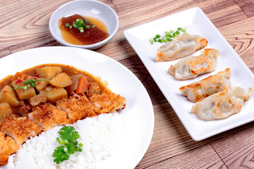 Rice with fried dolly fish topped yellow curry and Gyoza .