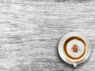 Coffee cup on wooden background textured.
