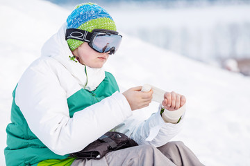 Young man sitting on the snow with snowboard