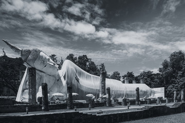 Buddha reclining or lie down to rest outdoor park at the temple in Thailand Black and white photography